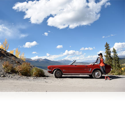 D5500 photo of a woman leaning on an a red convertible car in the desert under a blue sky